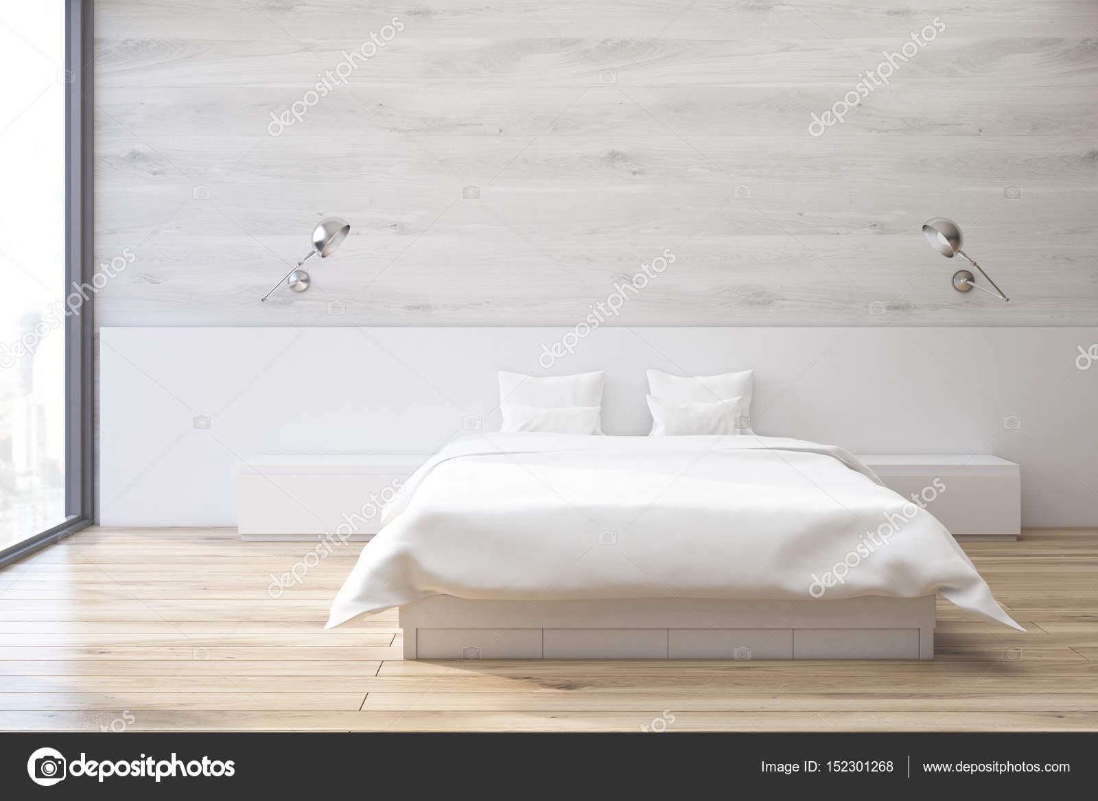 interieur van de minimalistische slaapkamer met een tweepersoonsbed staande in de buurt van een grijze muur