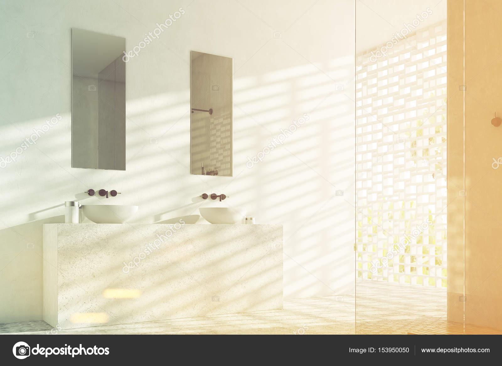 Vista laterale di un bagno con due lavelli e strette specchi