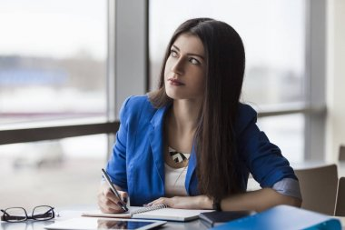 Pensive businesswoman writing in notebook
