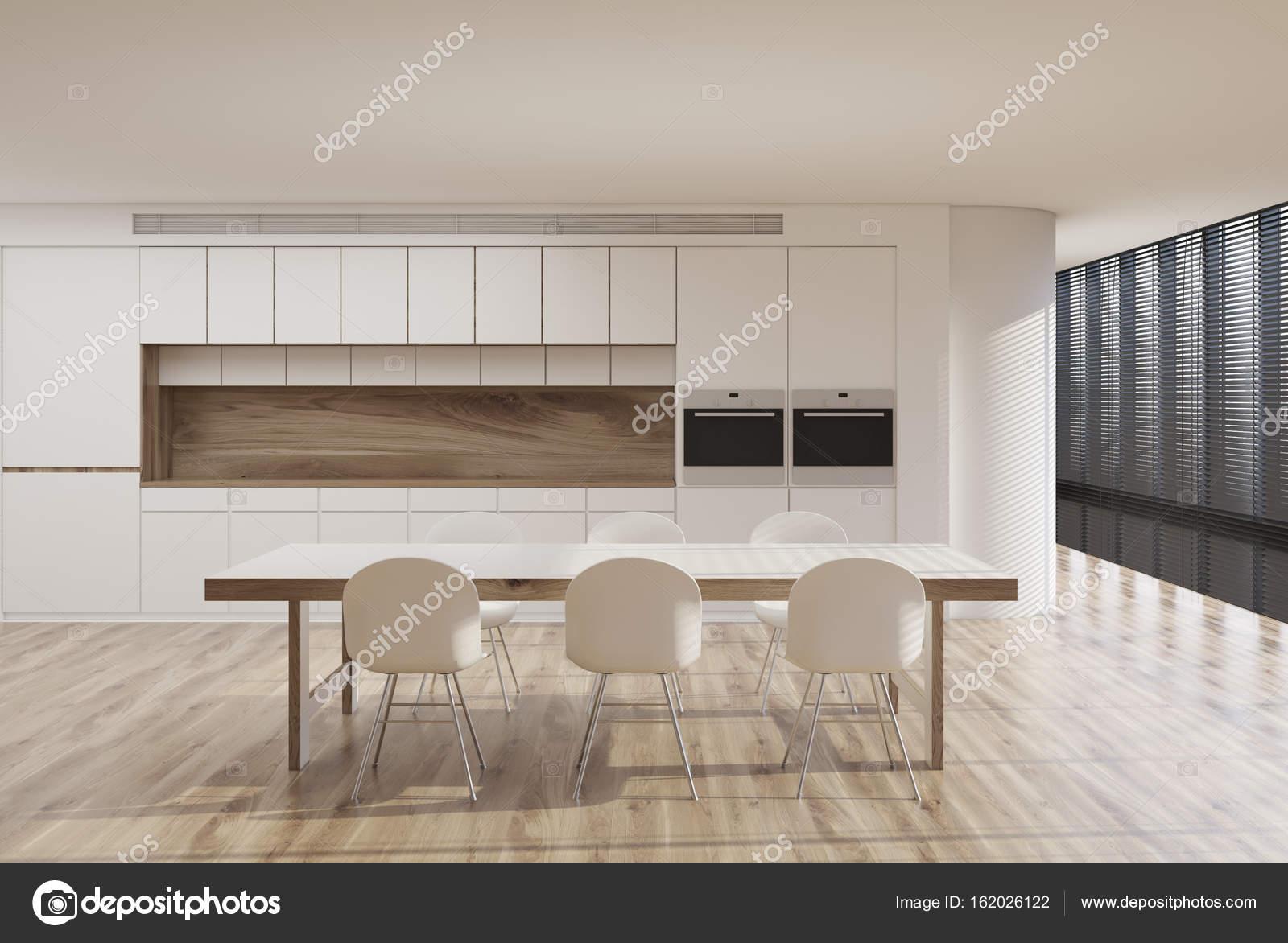 Weiße Küche Interieur Mit Einem Panoramafenster, Schatten, Ein Langer Tisch  Mit Weißen Stühlen Um Ihn Herum, Eine Arbeitsplatte Und Zwei In Öfen Gebaut.