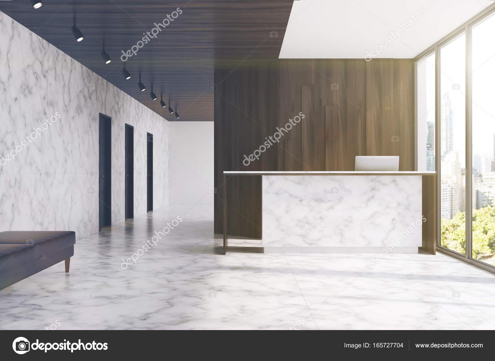 Réception en marbre dans un bureau de bois sombre aux tons
