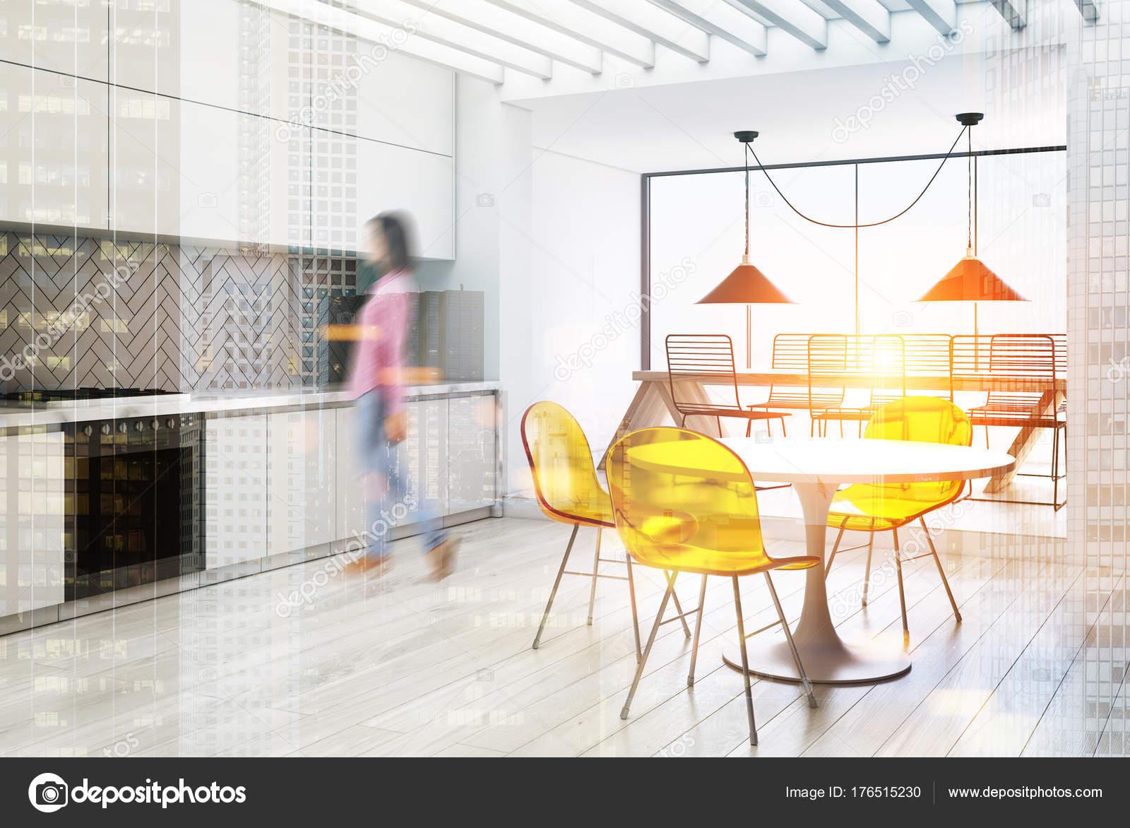 Weiße Küche Und Ein Esszimmer Ecke Mit Grauen Arbeitsplatten Und Schränken,  Ein Langer Tisch Mit Metall Stühle Und Ein Runder Tisch Mit Gelben Stühle.