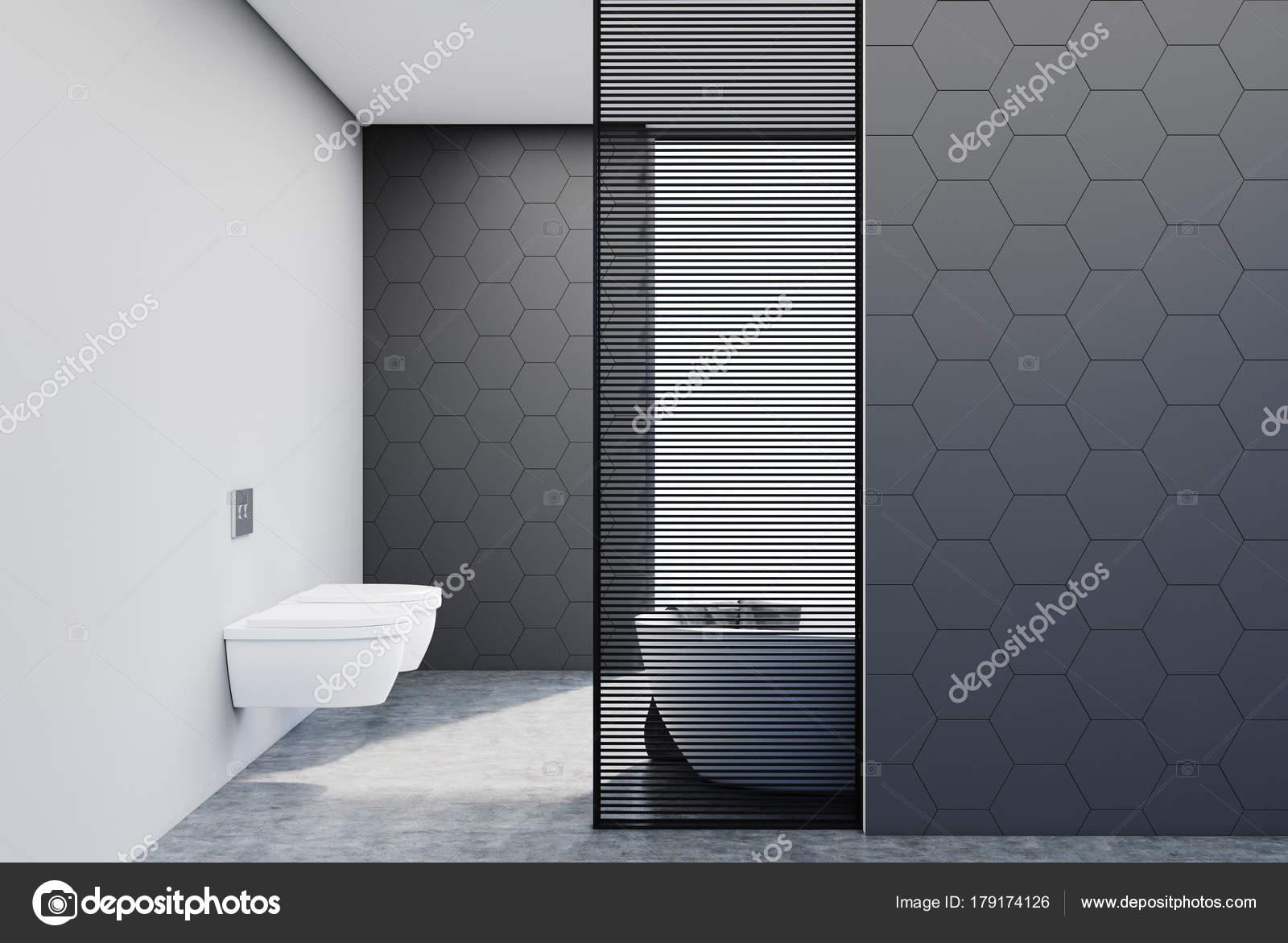 Bagno rivestito di piastrelle grigie vasca e wc u foto stock