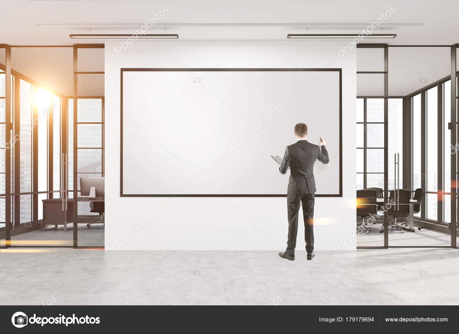 Homme d affaires à un tableau blanc dans le bureau de dessin