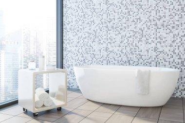 Gray tile bathroom corner, white tub