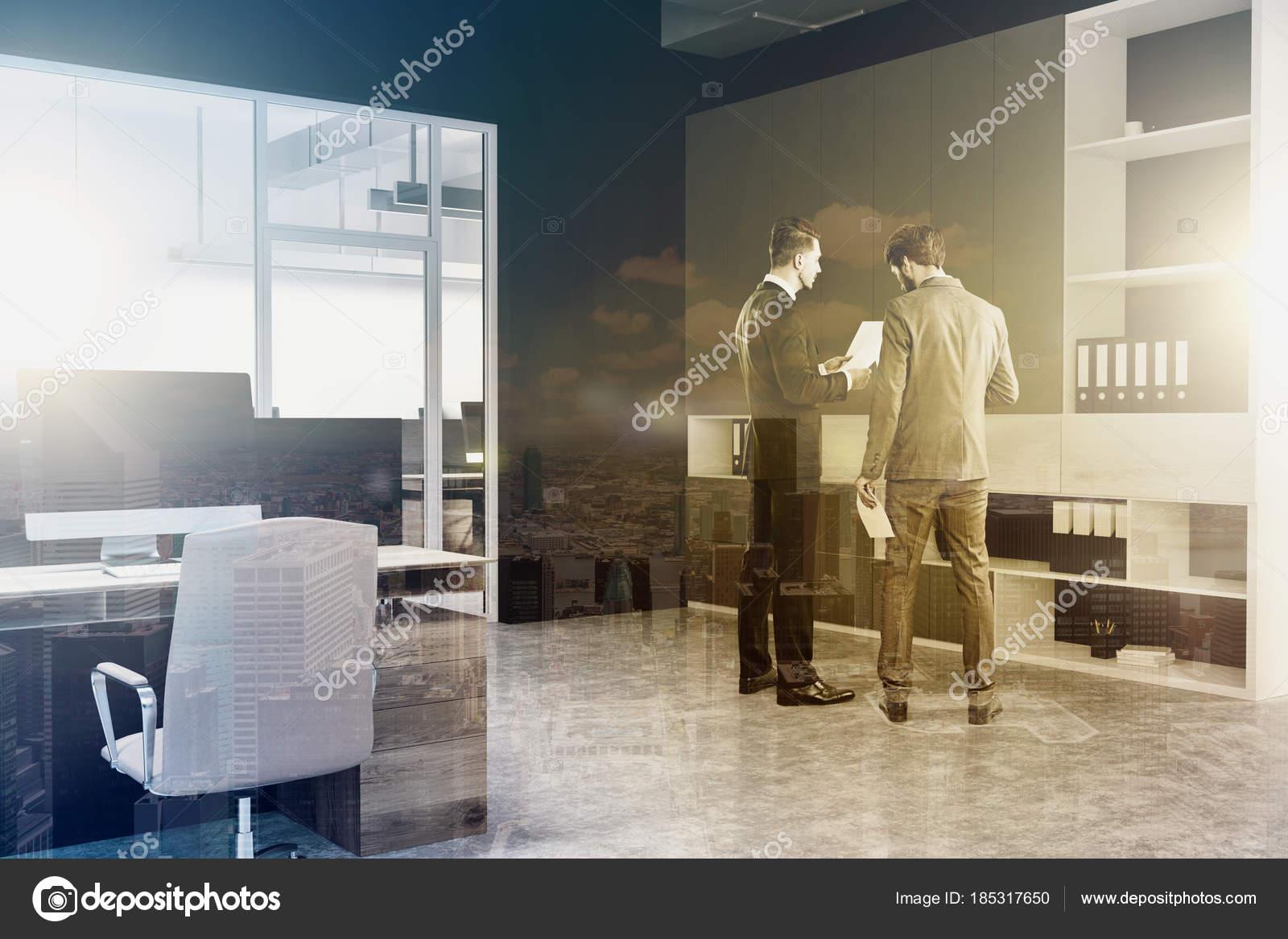 de hoek van de moderne kantoor met rijen houten computer desks zwarte muren en een betonnen vloer een boekenkast in de hoek mensen uit het bedrijfsleven