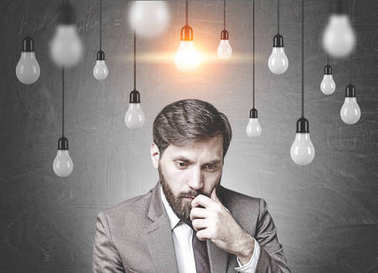 Bearded businessman in doubt, light bulbs