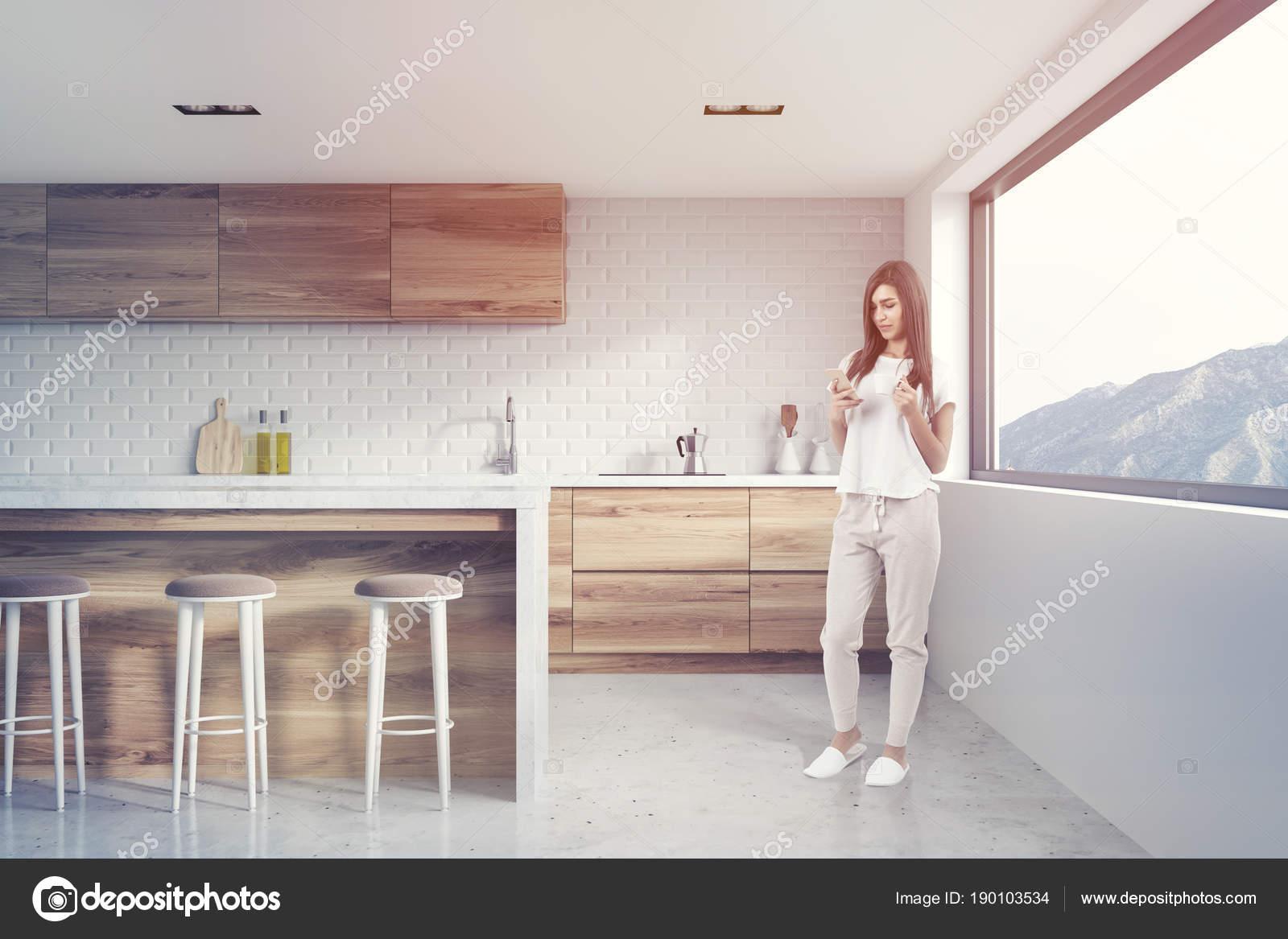 Intérieur De Cuisine Briques Blanches Avec Un Plancher De Béton, Des  Comptoirs En Bois Et Une Grande Fenêtre Avec Une Vue Parfaite. Une Femme.