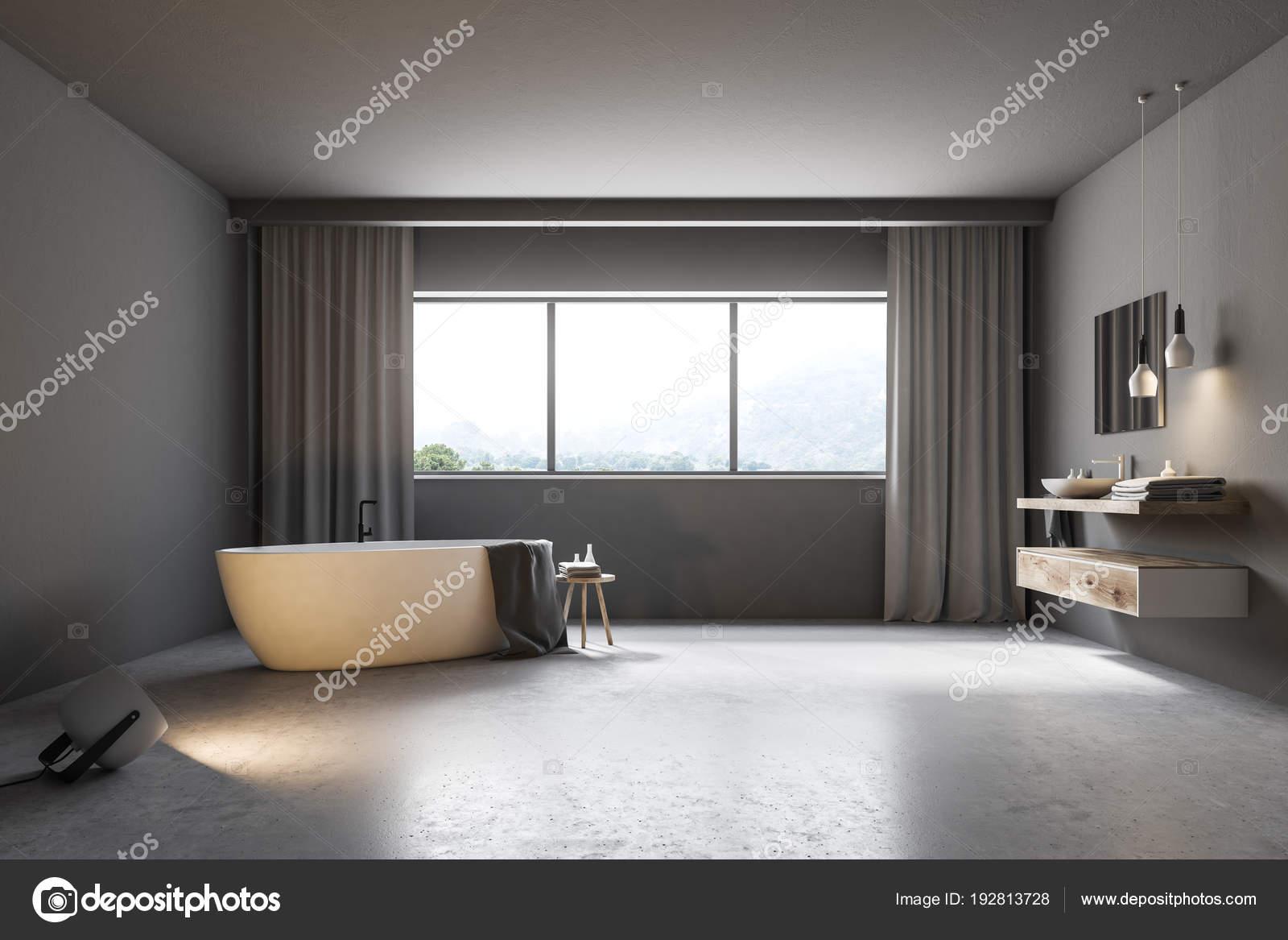 grijze badkamer interieur met een betonnen vloer een groot raam met grijze gordijnen een witte badkuip en een wastafel