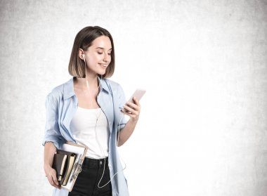 Beautiful student girl with books and smartphone