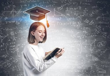 Cheerful young college student in casual clothes holding open copy book in her hand standing near blackboard with formula and graduation hat. Concept of science and career stock vector