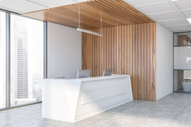 Comfortable white reception desk with computers standing in stylish corporate office corner with white and wooden walls and panoramic window with blurry cityscape. 3d rendering