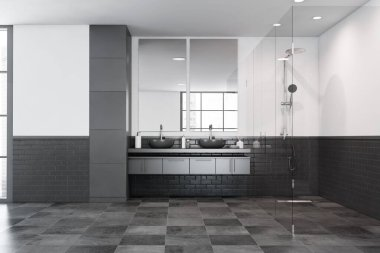 Interior of modern bathroom with white and black brick walls, tiled floor, comfortable grey double sink with two vertical mirrors and glass wall shower stall. 3d rendering