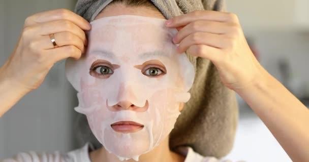 Žena s ručníkem na vlasech nanášení kosmetického plechu maska na obličej, pohled zepředu.
