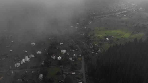 aerial drone top down footage, flying down from inside fog, revealing idyllic village, huts in line, green mountains and river in thee background.
