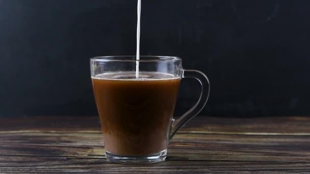 Mléko se nalévá do skleněného kelímku s kakaem, pomalé míchání.