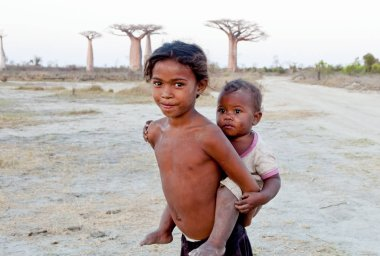 Madagascar-shy and poor african girl with infant on her back