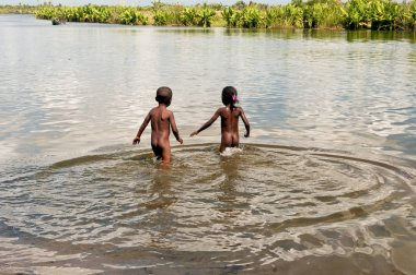 Poor african children playing in river, Madagascar