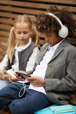 African schoolboy in headphones using mobile phone and listening to music while sitting on the bench together with girl outdoors