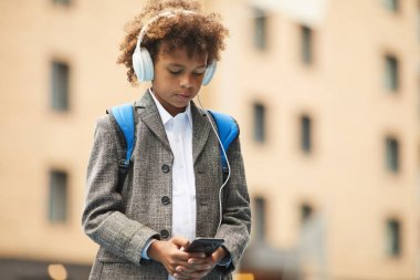 African schoolboy in headphones listening to music on mobile phone while standing outdoors