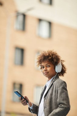 Portrait of African schoolboy in headphones holding mobile phone and looking at camera while standing outdoors