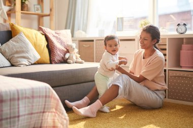 Happy young mother sitting on the floor smiling and playing with child in the living room