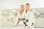 Két kimonós fiú portréja, amint egymás mellett állnak és ölelkeznek és mosolyognak a kamera előtt a karate verseny után.