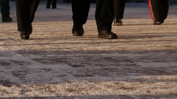 Feet of people walking on the city street on a winter day