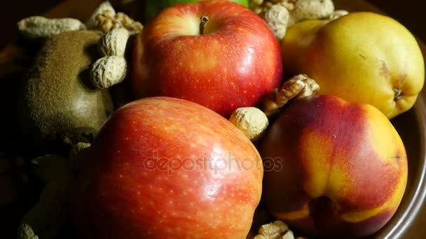 Jablka, broskve, hrušky, kiwi a ořechy na talíři