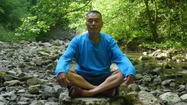 asiatischer Mann meditiert in einem schönen Wald