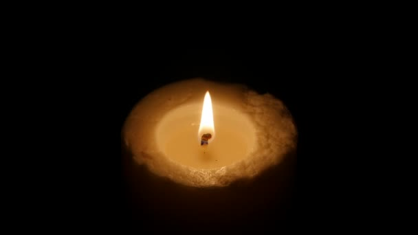 A large Candle burns in the dark. Black background