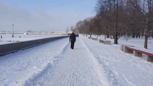 An old woman walks alone along the embankment on a winter day
