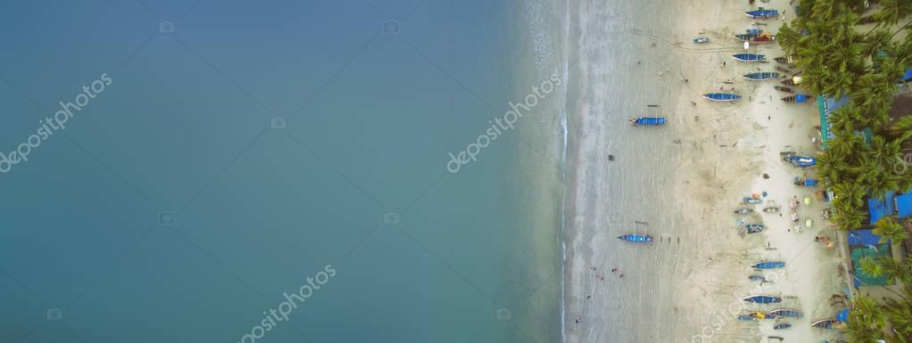 Aerial view of beautiful coastline of Indian ocean with tropical forest, sandy beach, calm blue water and fishing boats in Goa