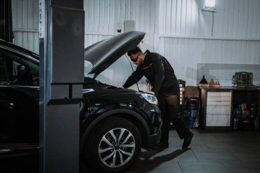 Good looking mechanic guy looking at the car engine in a car service