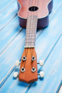 Close up of ukulele on blue wooden background