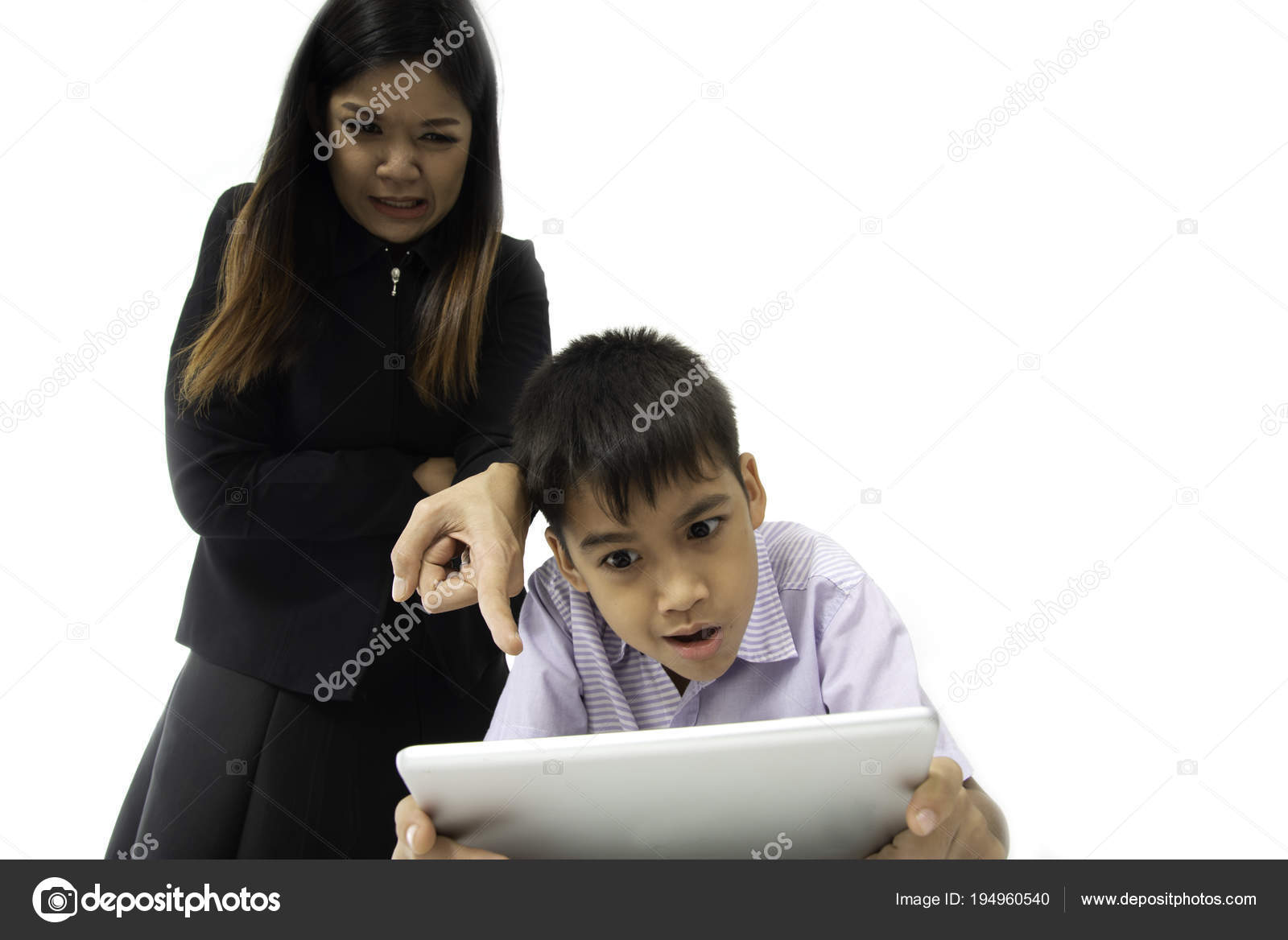 Angry Mother Nags While Boy Playing Tablet Game Stock Photo