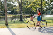 Cute girl walking with bicycle in daylight at a park.