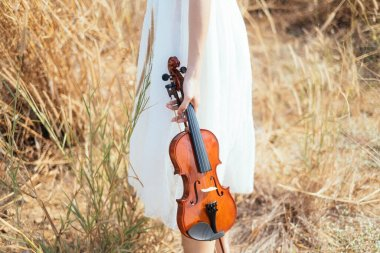 Girl on white dress with violin.