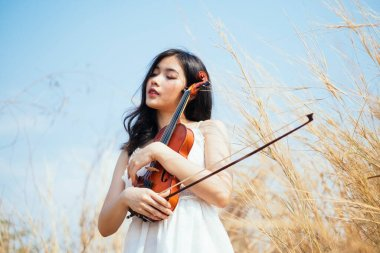 Girl on white dress with her violin.