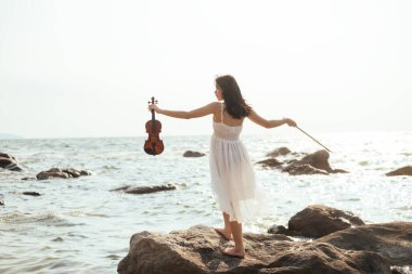 Girl standing on sea rock and her violin.