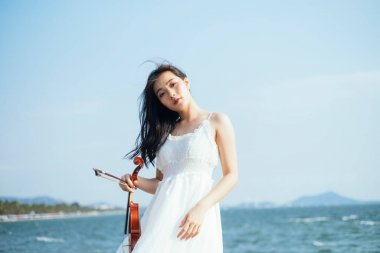 Girl carrying violin and sea on background.