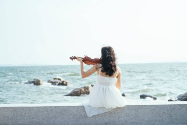 Girl playing violin next to the sea.