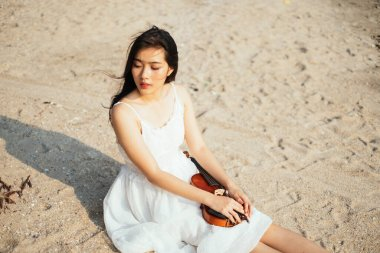 Portrait of young girl sitting on the beach with violin.