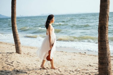 Thai woman walking forward to the sea with her violin.