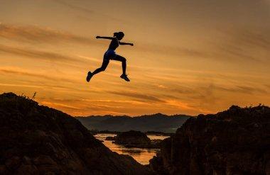 Woman jump through the gap between hill