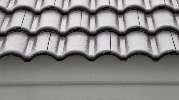 Dešťová voda stéká po střeše. Dešťová voda teče po střeše.