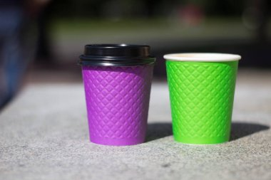 purple and green paper coffee Cup on the stove.