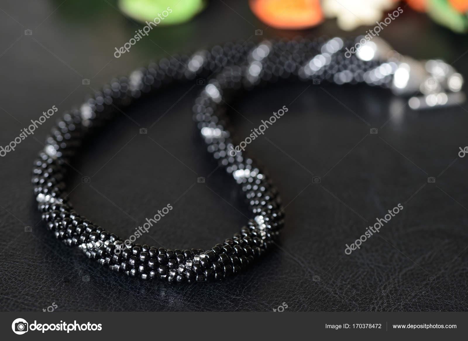 2edb7eedf6ea Collar de perlas negro con línea de plata sobre un fondo oscuro– imagen de  stock