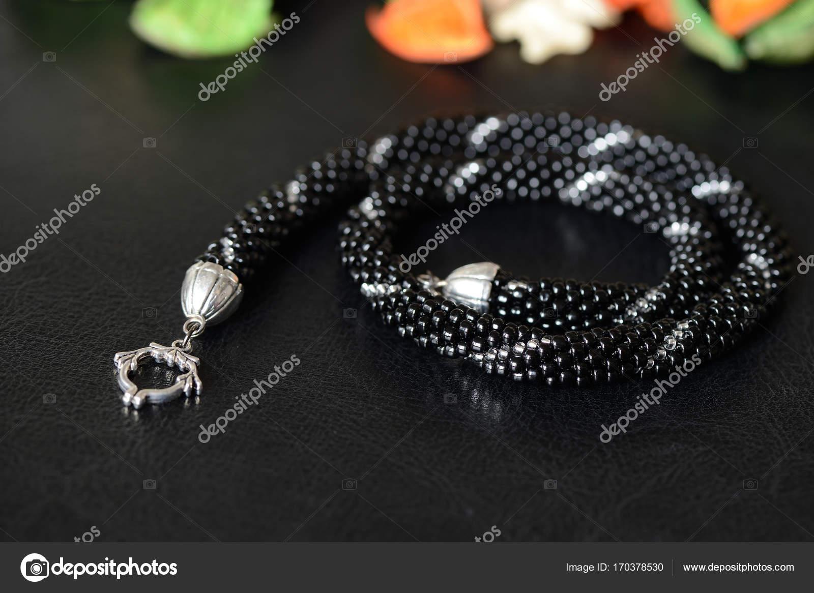 cbdac1c80d53 Collar de perlas negro con línea de plata sobre un fondo oscuro– Imagen de  Archivo