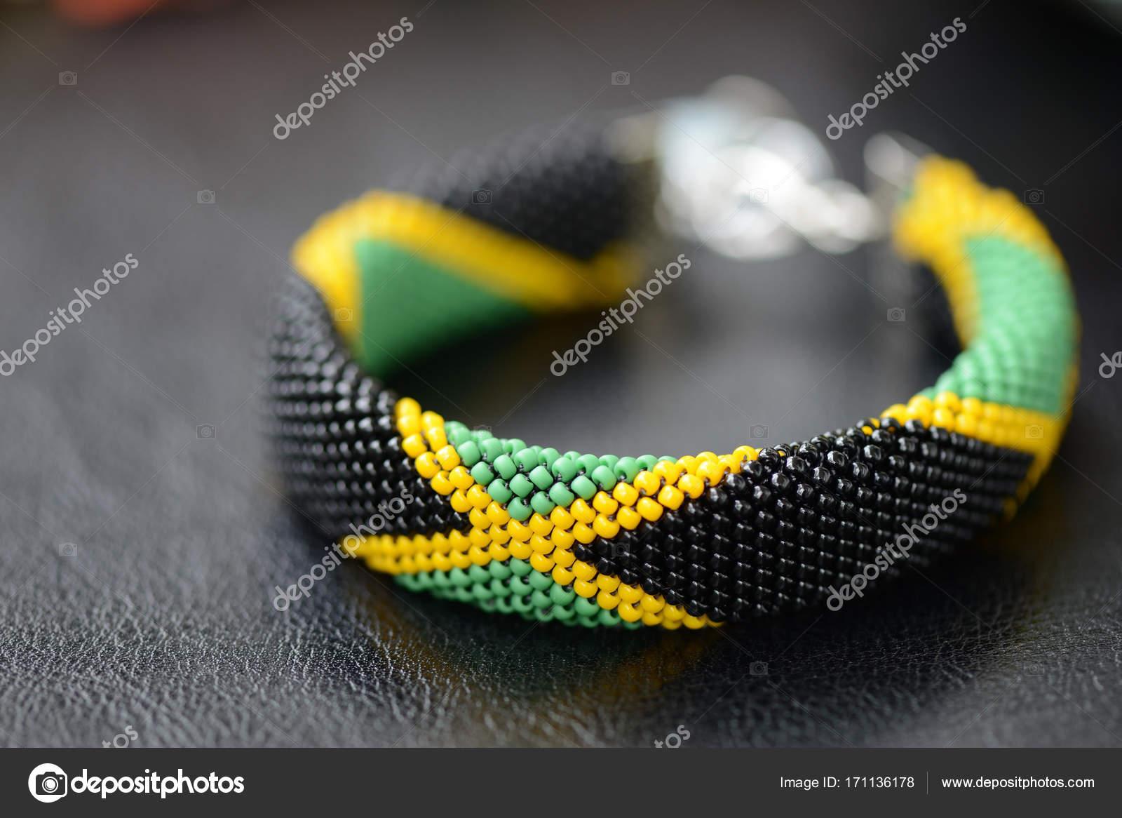 ab6b9aab4 Korálek háčkování náramek v barvách vlajka Jamajka na tmavém pozadí– stock  obrázky
